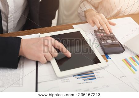Closeup Of Business Colleagues Hands Counting On Calculator And Using Digital Tablet With Blank Scre