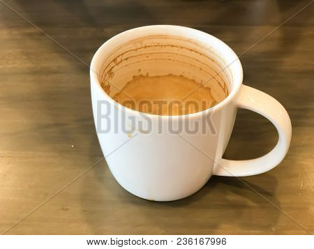 Close Up Dirty Coffee Cup On Wooden Table After Drinking In The Morning In Vintage Style