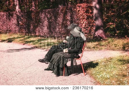 April, 19, 2014, Haarzuilens, The Netherlands: Costumed Couple Enjoy The Sun On A Bench In The Park
