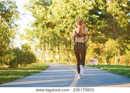 Backview Of Sporty Girl Running Along Racetrack In The City Park. Having Slim Body, Stunning Figure,