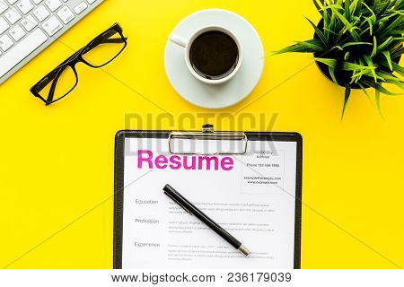 Review Resumes Of Applicants. Resume On Yellow Work Desk With Coffee, Glasses, Keyboard Top View.