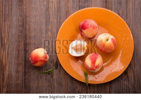 Fresh Peaches On A Wooden Table. Fresh Peaches In An Orange Plate On A Wooden Table.