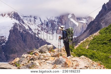 Young Man Admiring The Immensity Of Mount Torre And Torre Lake, In A Cloudy But Sunny Summer Day, In