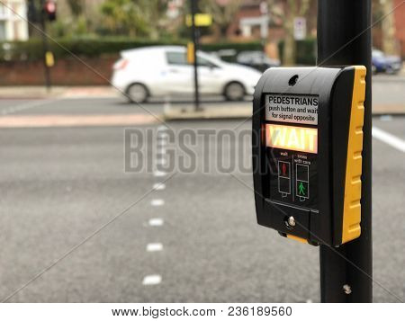 LONDON - APRIL 11, 2018: Pedestrian road crossing push button and illuminated wait instruction sign at an intersection in Camden, North London, UK.