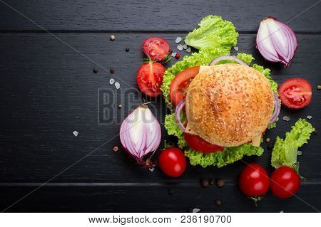 Beef Burgers With Vegetables. Lies On Black Textured Background With Lettuce, Tomatoes And Spices. T