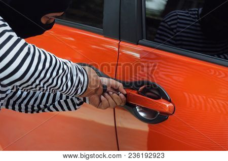 Close Up Of Hand Of Thief In Black And White Jacket Using Screwdriver To Open Car Door To Stealing A