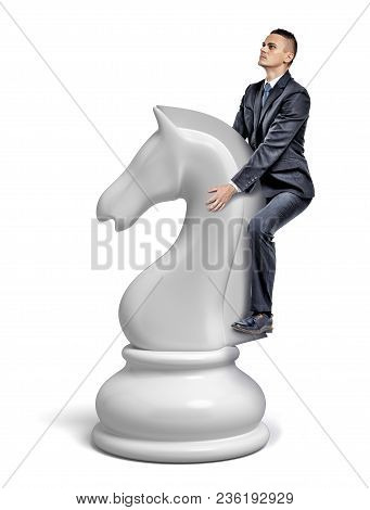 A Small Businessman Rides A Giant White Chess Knight Figure As A Horse. Back To Saddle. Business And