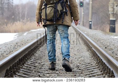 A Man With A Large Backpack Goes Ahead On The Railway Track During The Winter Season