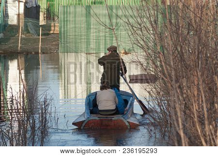 Russia, Balashov April 14, 2018. People In A Boat Sail Along A Flooded Street To Their House. Sunken