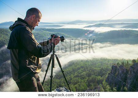 Photographer Takes Photos With Camera On Tripod On Rocky Mountain Peak. Beautiful Misty Sunrise And
