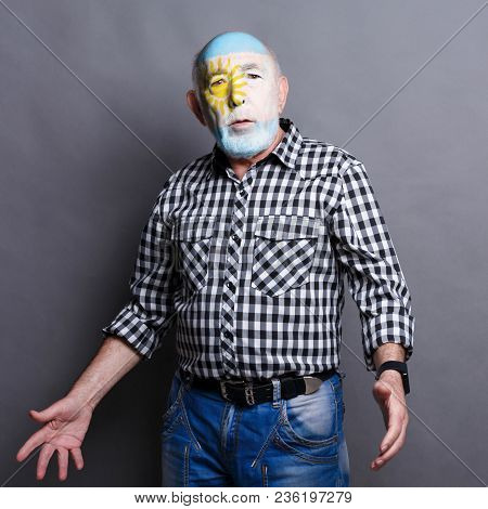 Portrait Of Sad Man With The Flag Of Argentina Painted On His Face. Football Or Soccer Team Fan, Spo