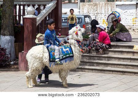 Huaraz, Peru - September 20, 2015: A Kid Sitting On Back Of A White Alpaca