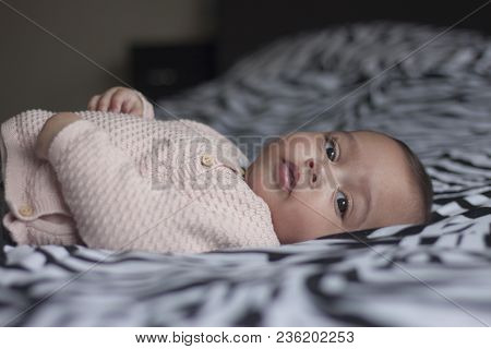 Portrait Of A Five Months Old Sweet Baby Girl Lying On Back On Parents Bed Looking In The Camera