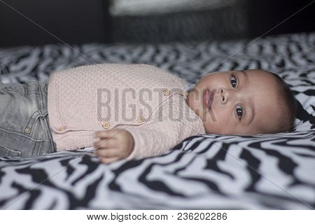 Portrait Of A Five Months Old Baby Girl Lying On Back On Parents Bed Looking In The Camera