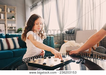Child Girl Playing Checkers With Her Dad At Home. Fatherhood And Quality Family Time Concept