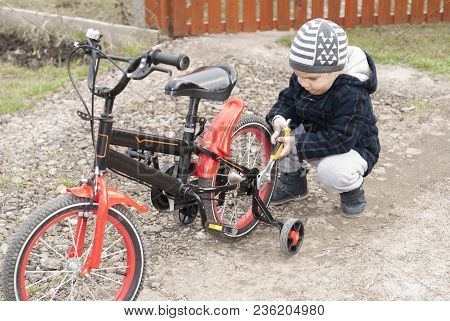 Little Boy Is Repairing A Bicycle