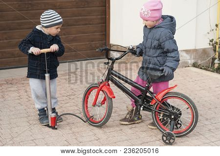 Little Boy Pumps A Bicycle Wheel For His Sister