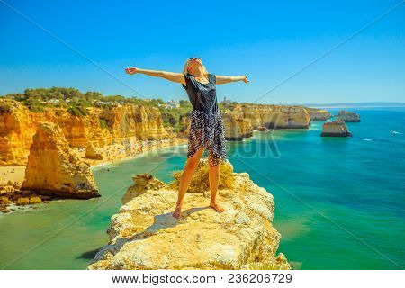 Tourism In Algarve. Freedom Lifestyle Tourist On Promontory Above Scenic Praia Da Marinha. Caucasian