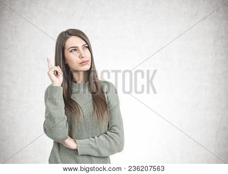 Thoughtful Young Woman With Long Dark Hair Is Wearing A Green Sweatshirt And Pointing Upwards With H