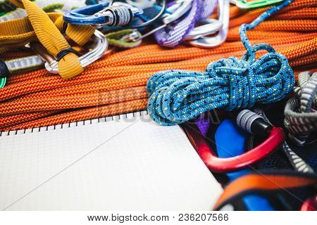 Notepad, Rope And Carbine. Equipment For Rock Climbing. Notebook And Equipment For Insurance And Tra
