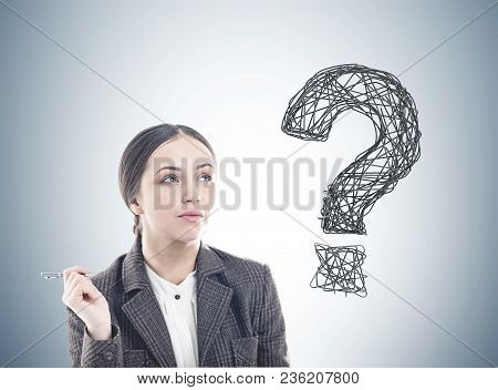 Pensive Young Businesswoman Wearing A Suit Is Holding A Pen And Thinking. A Large Question Mark Draw