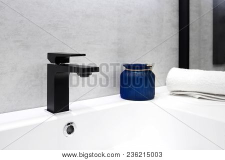 Gray Bathroom Interior With White Sink Black Modern Techno Style Faucet Blue Glass Jar And White Tow