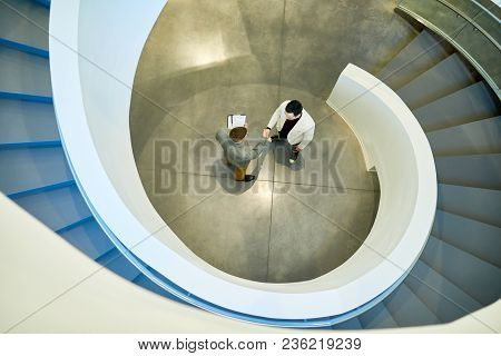 Directly Above View Of Business Partners Shaking Hands After Successful Completion Of Negotiations,