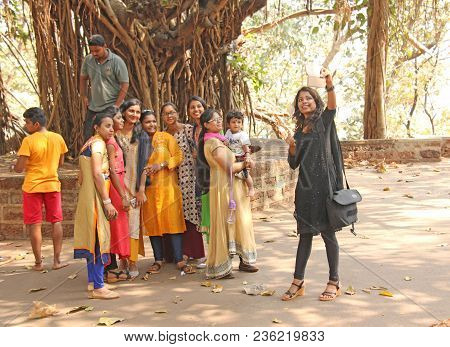 India, Goa, January 18, 2018. A Group Of Indian Girls On A Background Of A Large Sacred Banyan Tree