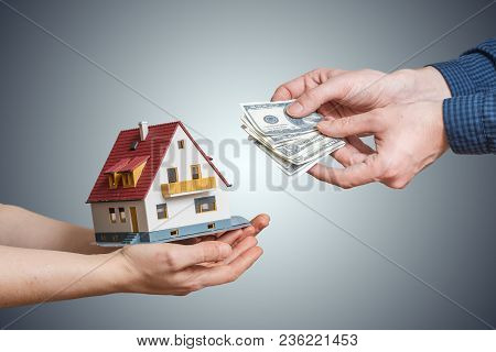 Sale Of House And Mortgage Concept. Hands Passing Money And Small House.