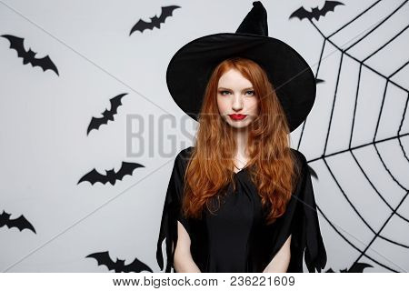 Halloween Concept - Beautiful Serious Witch With Angry Facial Expression Over Grey Background