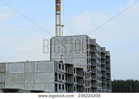 Unfinished Tall House With A Tower Crane Against The Sky