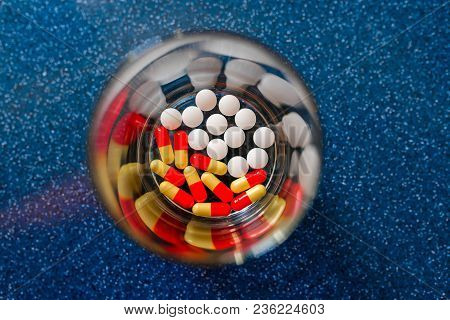 Colorful Pills And Medicines In Glass Plate On Blue Background. Different Pills And Another Drugs Ca