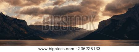 Banff national park Lake Minnewanka panorama at sunrise with mountains and forest in Canada.