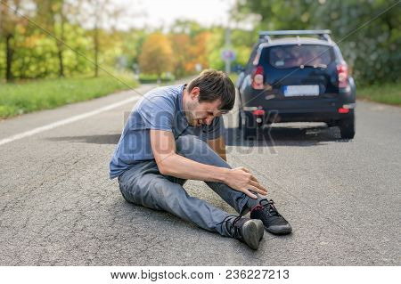 Hit And Run Concept. Injured Man On Road In Front Of A Car.