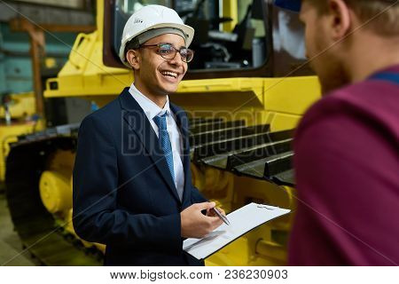 Smiling Mixed-race Inspector Wearing Suit And Hardhat Having Small Talk With Industrial Engineer Whi