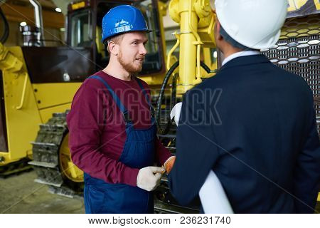 Profile View Of Hard-working Technician Wearing Hardhat And Overall Standing At Spacious Warehouse O