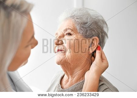 Otolaryngologist putting hearing aid in senior woman's ear on light background