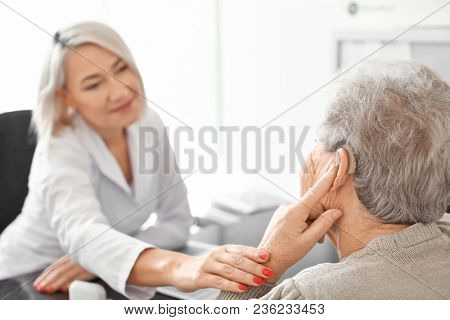 Senior woman adjusting hearing aid in doctor's office