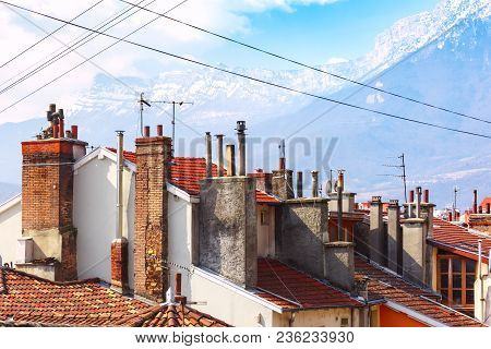 Typical French Tiled Roofs And Chimney Pipes In The Background Of The Alps Mountains, Grenoble, Fran