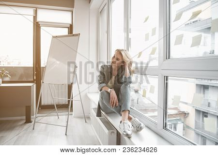 Meditative Woman Resting Near Casement In Office. She Is Wearing Casual Clothing And Smartwatch