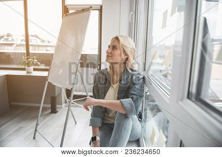 Blonde Woman Relaxing Near Window. She Is Having Pensive Face. Whiteboard On Background