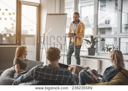 Man With Serious Expression Standing Close To Whiteboard And Listening To His Coworkers. They Sittin