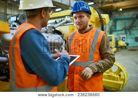 Two Young Technicians Wearing Reflective Vests And Hardhats Using Digital Tablet While Discussing Ho