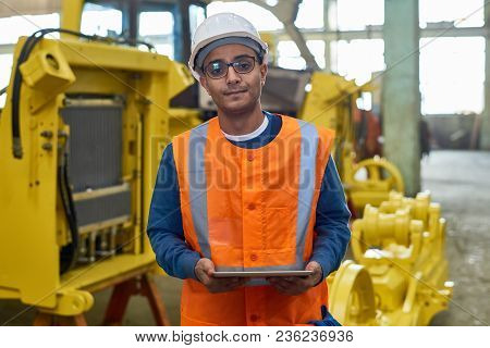 Waist-up Portrait Of Handsome Mixed-race Machine Operator Wearing Reflective Vest And Hardhat Lookin