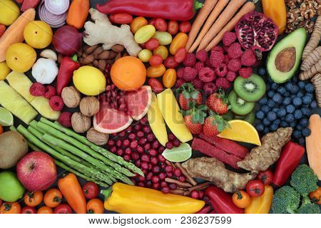 Fruit and vegetable health food to maintain a healthy heart with super foods high in antioxidants, anthocyanins, fibre, vitamins and minerals. Top view background.