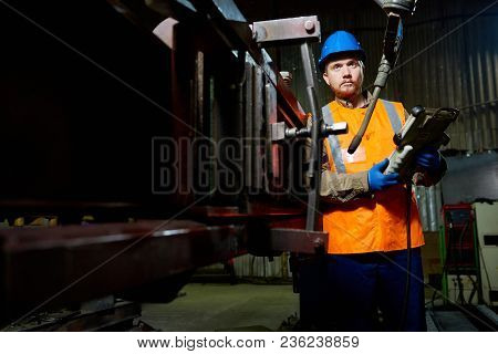 Full Length Portrait Of Confident Bearded Technician Wearing Reflective Vest And Hardhat Adjusting E