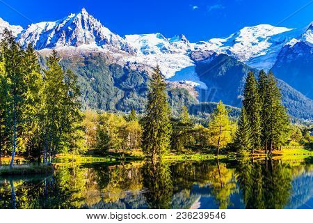 The lake reflected the snow-capped Alps and evergreen spruce. City Park is illuminated by the setting sun. Concept of active tourism. The mountain resort of Chamonix, Haute-Savoie