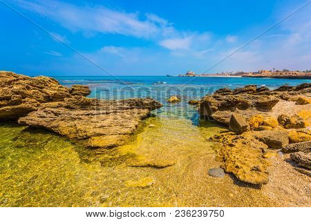 Flooded in the sea remains of ancient fortifications. Ruins of the ancient city and port of Caesarea. Spring day in Israel. Concept of archeological and historical tourism