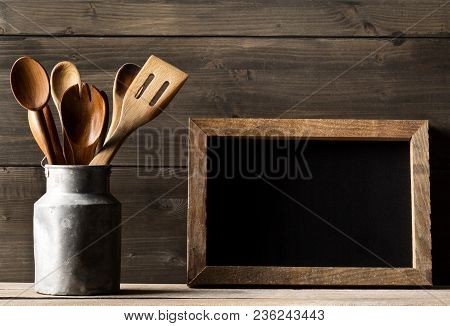 Wooden Kitchen Cooking Tools With Spoons And Spatula In Metal Can In Front Of Rustic Wooden Board Ba