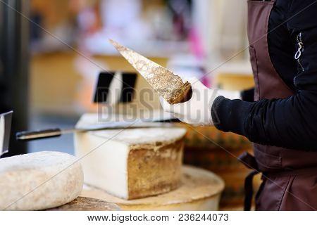 Seller Cutting Organic Cheese On Farmer Market In Strasbourg, France. Typical European Local Farmer